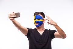 Selfie no telefone do fan de futebol do sueco no apoio do jogo de equipas nacionais da Suécia no fundo branco Imagem de Stock