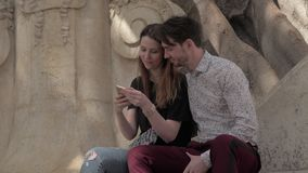 A selfie at an old wall. A young couple making selfie sitting at an old wall with stucco work stock video