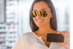Selfie in optic store. Beautiful young woman making selfie and smiling while standing in front of the mirror in the optic store stock images
