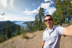 Selfie over the lake. Young man portrait in form of a selfie over Coeur d' Alene lake, Idaho, from the top of mineral ridge stock images