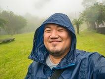 Selfie Photo of Asian fat trekker trekking to Khao Luang mountain Ramkhamhaeng National Park in rainy and foggy day. Sukhothai province Thailand stock image