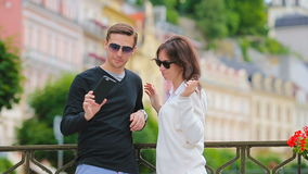 Selfie photo by caucasian couple traveling in Europe. Romantic travel woman and man in love smiling happy taking self