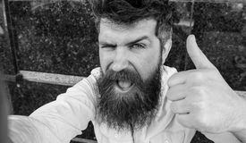 Selfie photo concept. Hipster, tourist with tousled hair and long beard looking at camera, taking selfie photo. Man. With beard on cheerful face shows thumb up stock photography