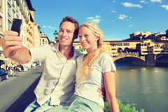 Selfie photo by couple traveling in Florence. Romantic travel women and men in love smiling happy taking self portrait outdoor by Ponte Vecchio during vacation stock photos