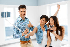 Selfie Photo. Friends Taking Picture With Smartphone Selfie Stic Stock Photography