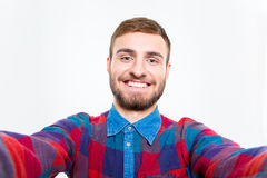 Selfie photo of happy smiling bearded guy in plaid shirt Stock Image