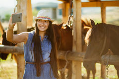 Selfie photo with horse. Happy woman taking selfie photo with horse royalty free stock image