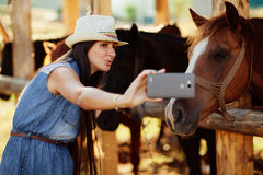 Selfie photo with horse. Happy woman taking selfie photo with horse with smartphone camera stock photo