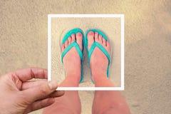 Selfie photo of woman feet wearing flip flops on a beach Stock Photography