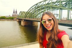 Selfie photo of young fashion woman in Cologne with Hohenzollern Bridge and Cathedral on the background, Cologne, Germany. Stock Photos
