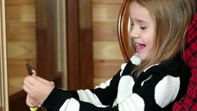 Selfie photos, cute little girl making photo mobile phone, the child uses the gadget to create photos stock footage