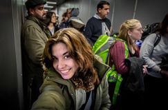 Selfie at the Plane Boarding. Girl taking a selfie while she is in the queue of the Boarding in the Plane. It is all crowded around her. Picture taken with a Stock Photos