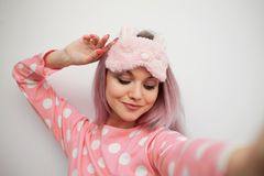 Selfie portrait of charming girl in pajamas and sleep mask. Woke up in the morning. Charge of vivacity stock photography