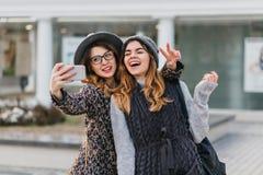 Selfie portrait of joyful fashionable girls having fun on sunny street in city. Stylish look, having fun, travelling stock photography