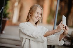 Closeup selfie-portrait student of attractive girl in sunglasses with long hairstyle and snow-white smile in city. Selfie-portrait student of attractive girl in Stock Image