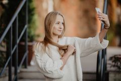 Closeup selfie-portrait student of attractive girl in sunglasses with long hairstyle and snow-white smile in city. Selfie-portrait student of attractive girl in Royalty Free Stock Photo