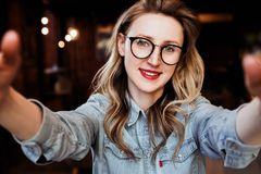Selfie portrait of young smiling woman sitting in cafe. Hipster girl in trendy glasses takes a selfie in coffee shop. royalty free stock image