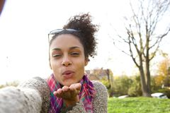 Selfie portrait of a young woman blowing a kiss Stock Photo