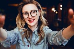 Selfie portret młody uśmiechnięty kobiety obsiadanie w kawiarni Modniś dziewczyna w modnych szkłach bierze selfie w sklep z kawą fotografia stock