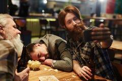 Selfie in pub. Young men with bottle of beer making selfie in pub Stock Image