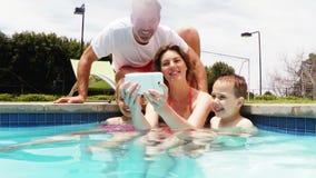 Selfie que habla de la familia del teléfono móvil en el lado de la piscina almacen de metraje de vídeo