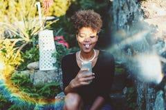 Selfie que toma femenino joven brasileño mientras que se sienta en parque Imagen de archivo libre de regalías