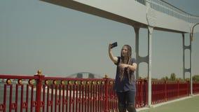 Selfie que toma femenino mientras que rollerskating en el puente almacen de metraje de vídeo
