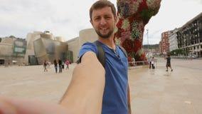 Selfie que toma turístico masculino cerca de la escultura enorme de la flor en Bilbao, España almacen de metraje de vídeo