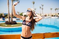 Selfie-retrato del primer de la muchacha morena atractiva con el sombrero de paja y las gafas de sol que colocan la piscina cerca imagen de archivo libre de regalías