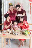 Selfie in Reunion Dinner. Celebrating Chinese New Year, taking selfie at reunion dinner. Happy Asian Chinese multi generation family with red cheongsam dining at Royalty Free Stock Photo