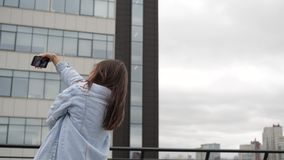 Selfie on the roof of a brunette. Girl dancing on the roof and shoots the phone stock video footage