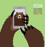 Selfie in Russia. Bear selfie. Bear paw holding a phone. Russian Royalty Free Stock Image