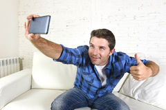 在家采取selfie图片或自已录影有手机的年轻可爱的30s人坐长沙发微笑愉快 库存照片