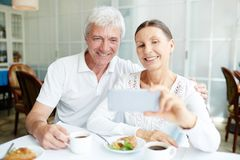 Selfie of seniors. Affectionate senior spouses making selfie by cup of coffee in cafe Royalty Free Stock Photo