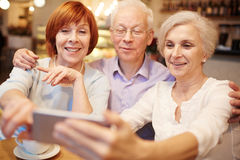 Selfie of seniors. Row of smiling pensioners making their selfie in cafe during hangout Stock Photo