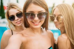 Selfie shot, three happy girls in sunglasses. Near the swimming pool. Resort holidays. Tanned women on summer holidays Stock Photos