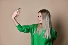 Το πορτρέτο κινηματογραφήσεων σε πρώτο πλάνο της νέας εύθυμης ξανθής γυναίκας μόδας στην ένδυση πουλόβερ κάνει selfie στο smartph στοκ εικόνες