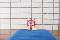 Selfie of Sneakers. Woman Wearing Jean Skirt and Red Shoes on Tile Background. Great for Any Use Royalty Free Stock Photo