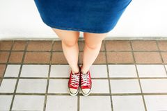 Selfie of Sneakers. Woman Wearing Jean Skirt and Red Shoes on Tile Background. Great for Any Use Stock Photo