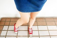 Selfie of Sneakers. Woman Wearing Jean Skirt and Red Shoes on Tile Background. Great for Any Use Stock Images