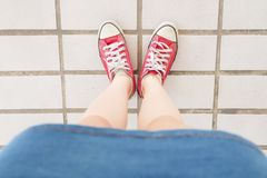 Selfie of Sneakers. Woman Wearing Jean Skirt and Red Shoes on Tile Background. Great for Any Use Stock Photos