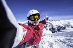 Selfie snowboarder. Young happy woman taking selfie with the smartphone on the top of the North Alps, France. stock photos