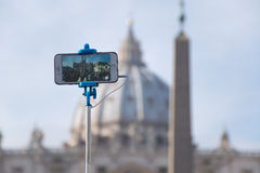 Selfie in St. Peter. Taking a selfie of the dome of St. Peter's Basilica in Rome in the background Royalty Free Stock Photos