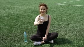 Selfie on a stadium lawn. Woman takes picture of herself sitting on a sport stadium lawn on smartphone camera stock video