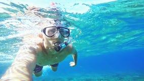 Selfie subacqueo Nuoto del giovane in una maschera subacquea nel mare video d archivio