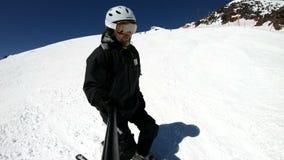 Selfie szerokiego kąta męska narciarka starzał się w czarnym wyposażeniu i biały hełm jedzie na śnieżnym skłonie na słonecznym dn zbiory