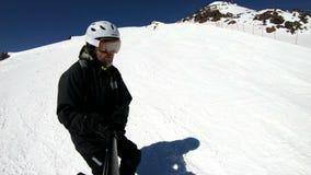 Selfie szerokiego kąta męska narciarka starzał się w czarnym wyposażeniu i biały hełm jedzie na śnieżnym skłonie na słonecznym dn zbiory wideo