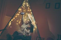 Selfie in a teepee. Mother and daughter sitting in a teepee, taking a selfie and playing Stock Image
