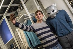 Selfie terwijl het winkelen Een kerel in een gestreepte sweater in een opslag met kleren neemt beelden van zich op de telefoon na royalty-vrije stock afbeeldingen