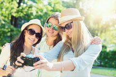 Selfie. Three attractive girls taking picture at summer holidays,. Girls with camera taking self-portrait on their travel vacation stock photography